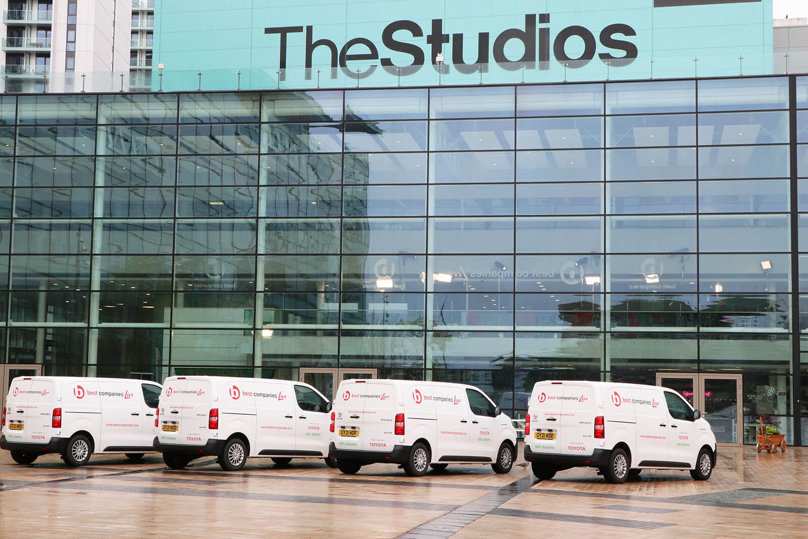 Four electric vans with Best Companies Live branding parked outside of the studio at Media City