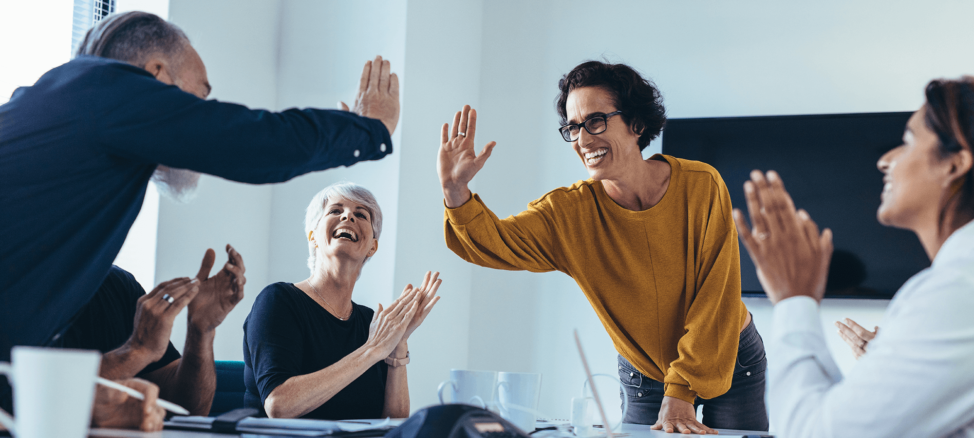 Group of colleagues in meeting celebrating and giving high-fives