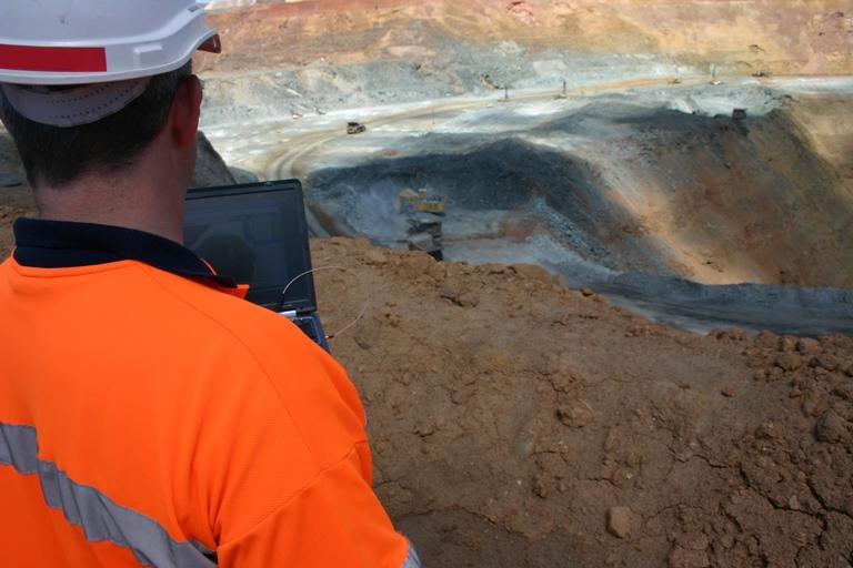 A mine worker observes current pit activity.