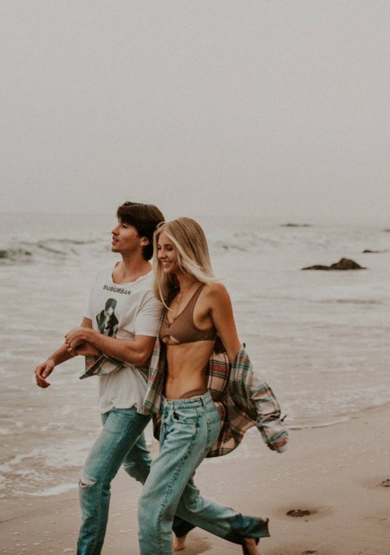 A shot of Nue Glow founders David Casey and Tallie Thompson walking together on the beach.
