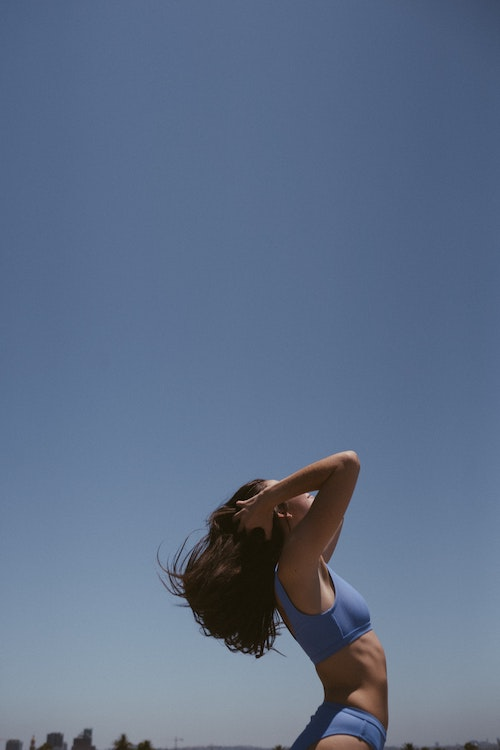 Woman in a blue bathing suite flipping her hair back on the beach. Shot from the side with the blue sky in the background.