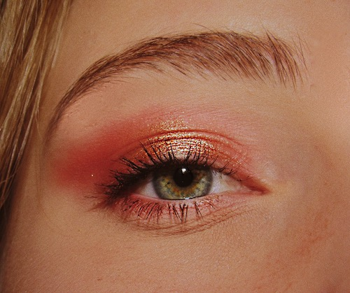 Up-close shot of a woman's eye, focusing on her pink eye shadow with touches of gold.