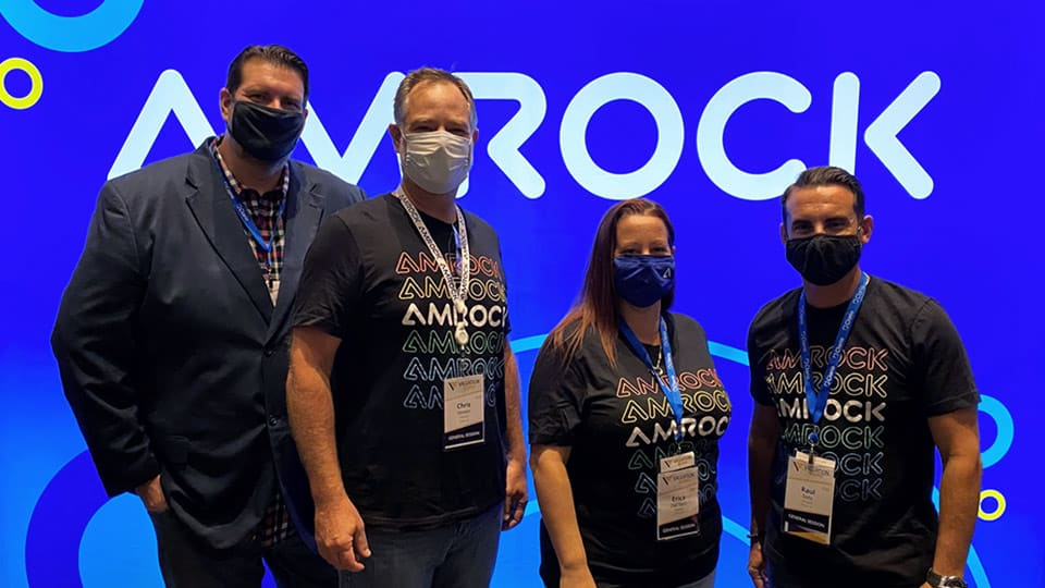 amrock appraisal team members at valuation expo 2021 in las vegas wearing masks and amrock t-shirts in front of lit amrock backdrop