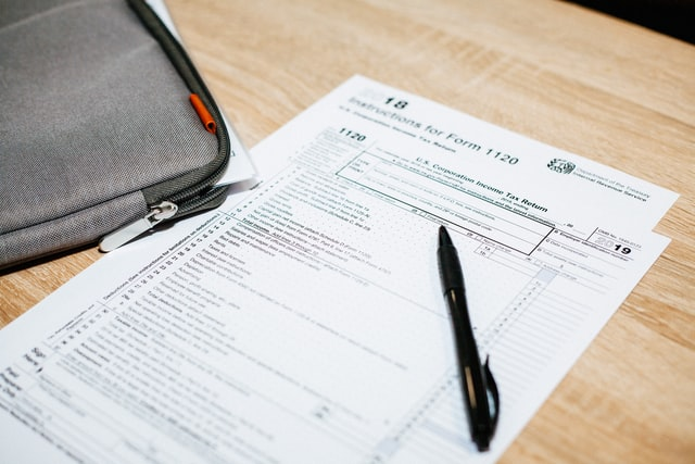 Image of a blank paper tax form on a light pine-colored desk.