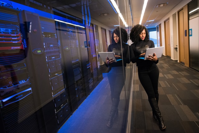 Image of woman with a computer standing near a large data center.