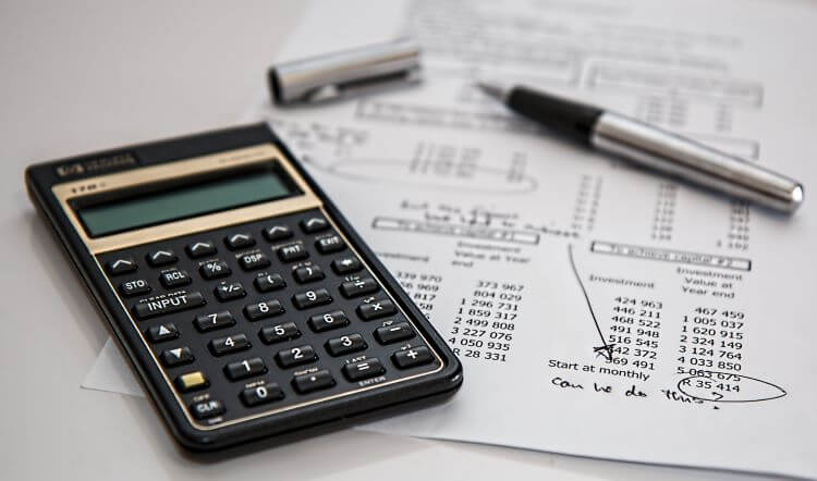 Image of an accountant's calculator near a pile of notated bank statements and an uncapped pen.