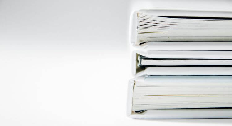 Image of binders full of paper against a white background.