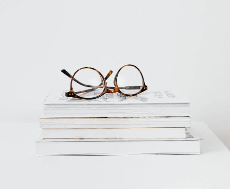 Image of glasses on top of a stack of white books in a white room.