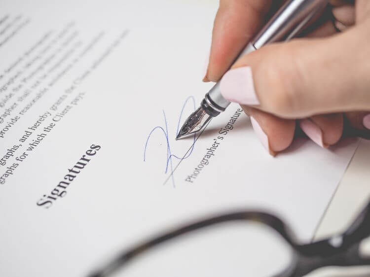 Image of a woman signing a 1099 contract.