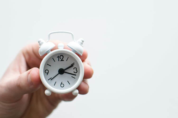 Image of a small white clock against a white background.