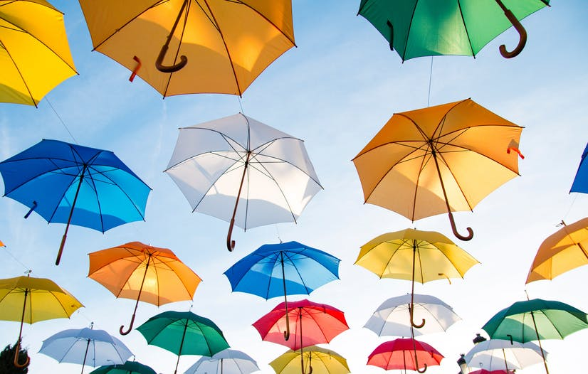 Image of colorful umbrellas against a bright blue sky.