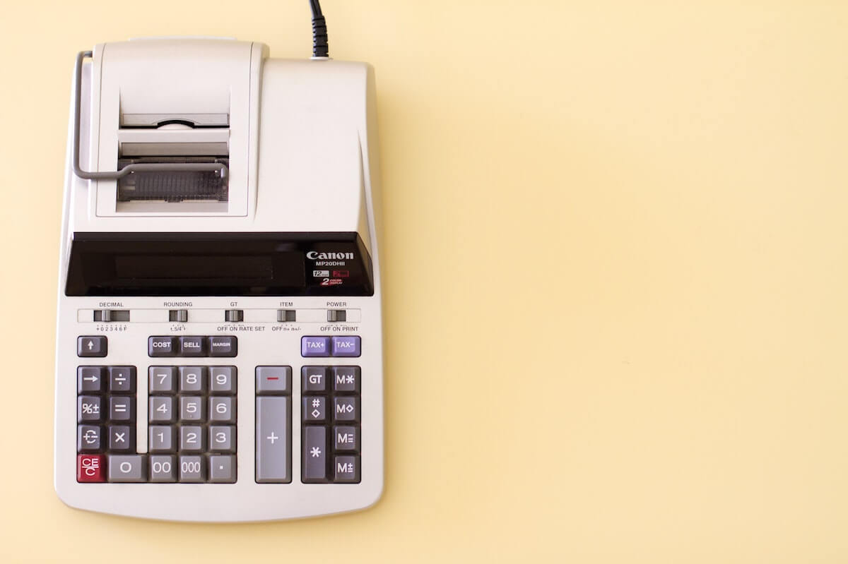 Image of a robotic-looking accountant's calculator against a light yellow creme background.