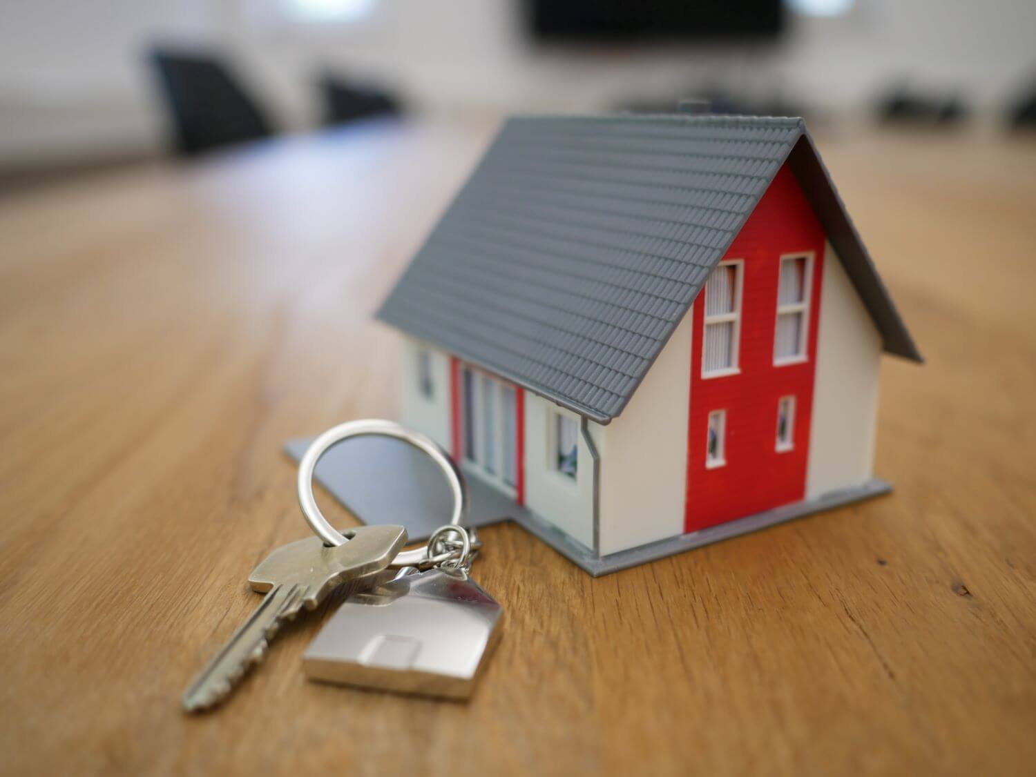 Image of a small wooden house and a person holding house keys.