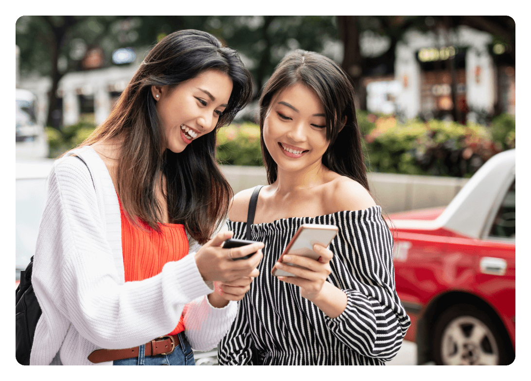 Two women using their phones