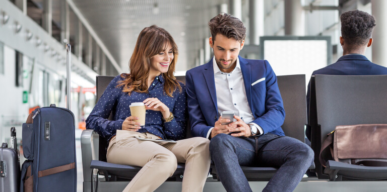 Couple sitting at airport using mobile phone