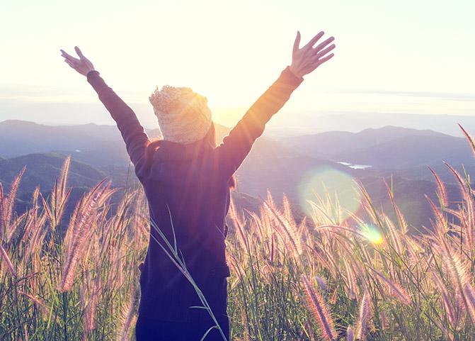 Jeune femme debout devant l'horizon les bras tendus vers le ciel