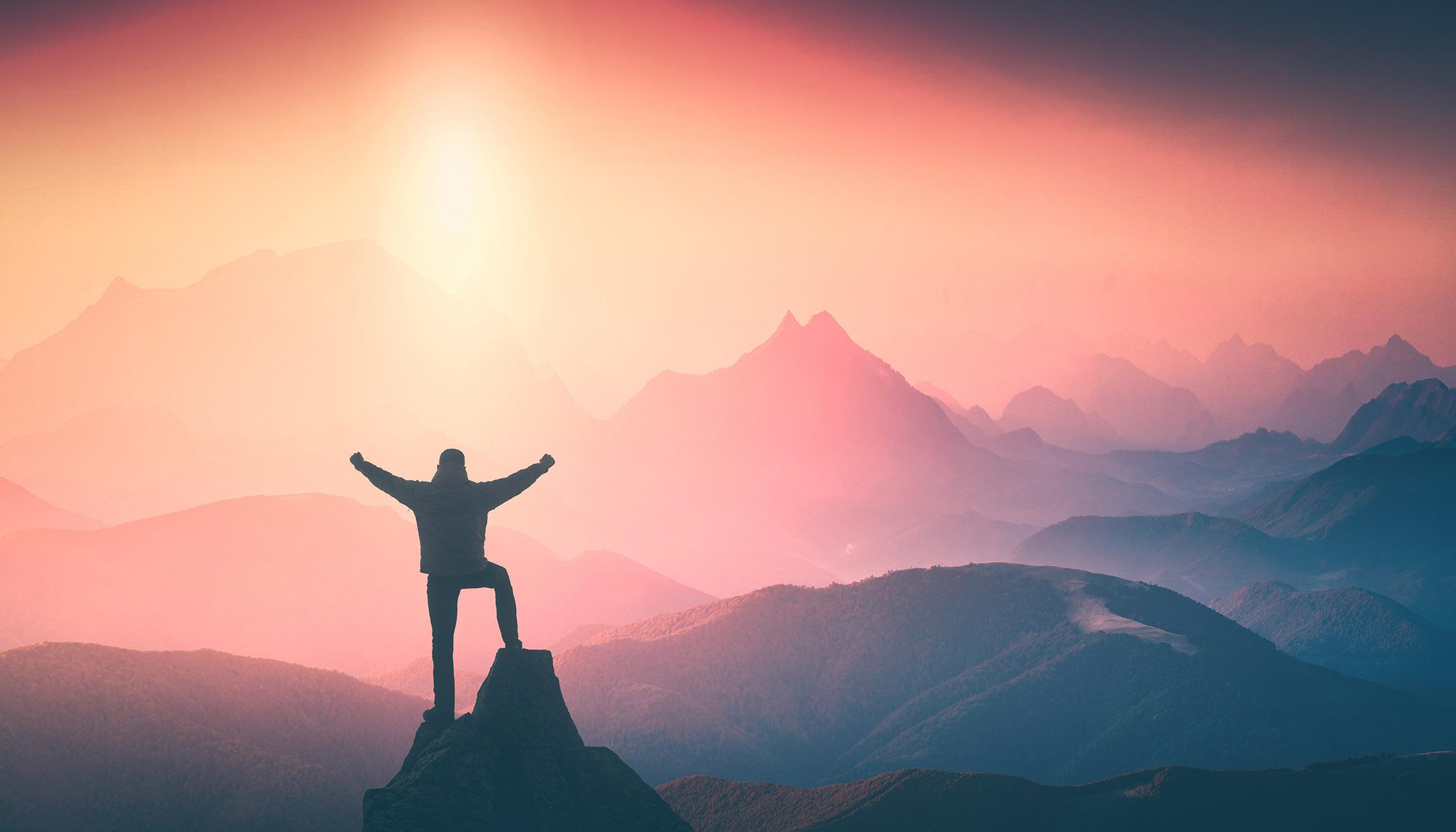 Homme debout regardant les montagne au levé du soleil