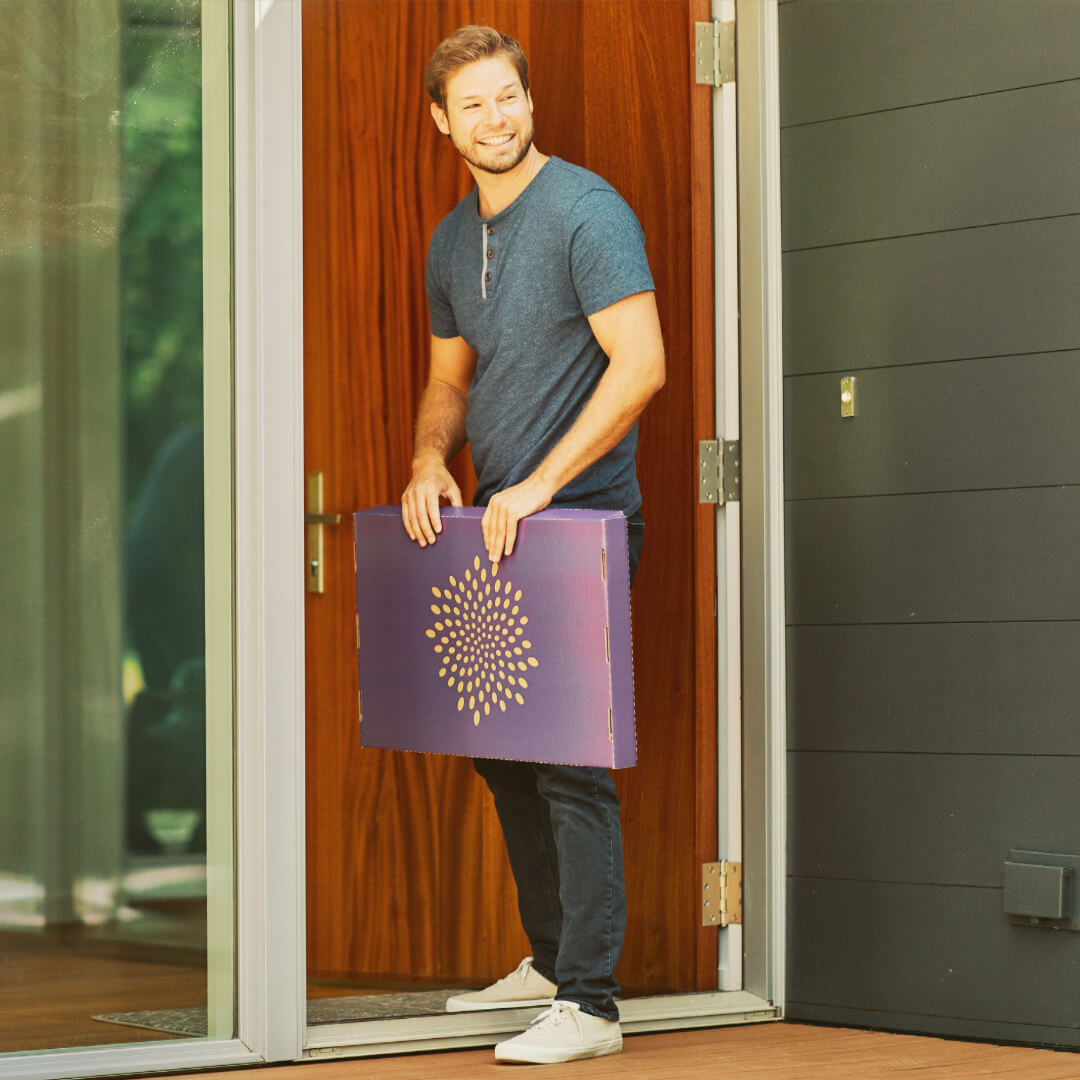 man picking up second nature air filter box off porch
