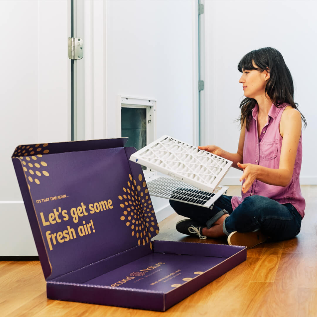 woman pulling second nature air filter out of box