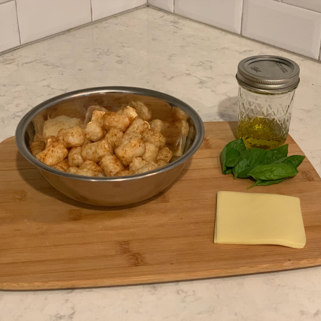 tater tots, cheese, and oil on a cutting board