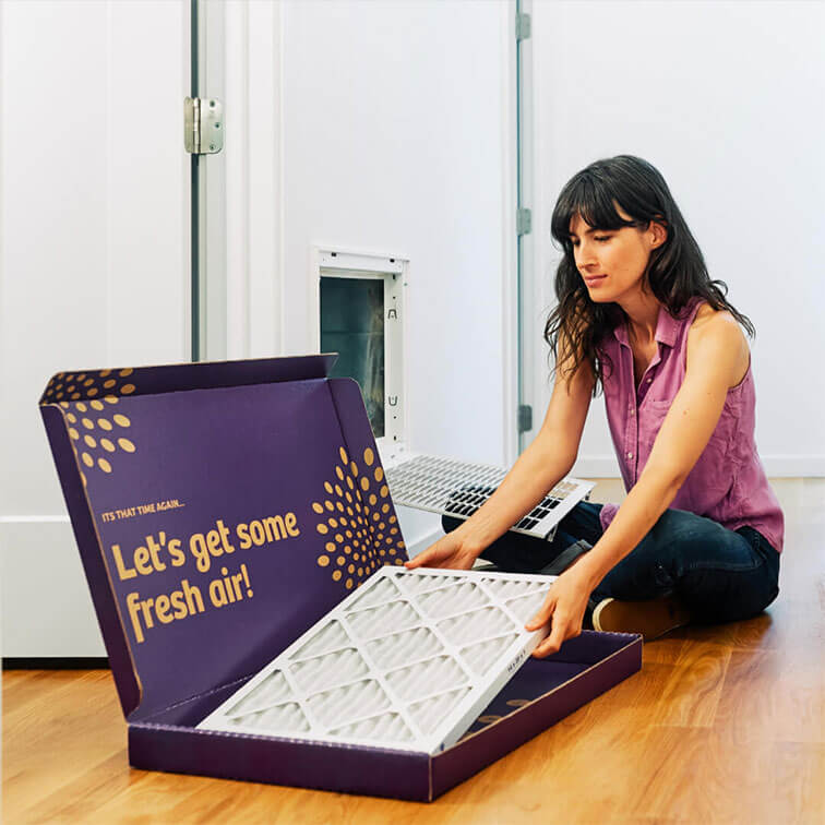 woman taking second nature air filter out of box