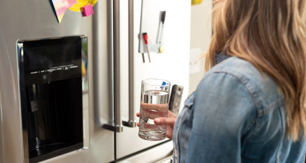 woman drinking clean water from her refrigerator