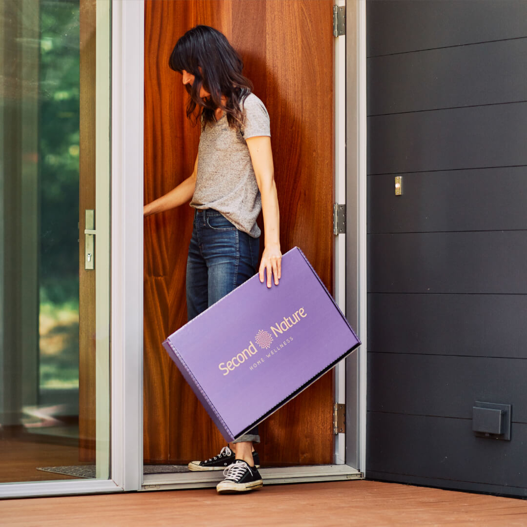woman picking up second nature box from the front porch