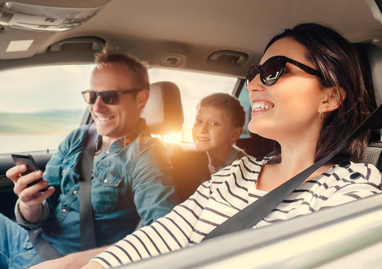 Familia feliz conduciendo en el coche durante la puesta de sol