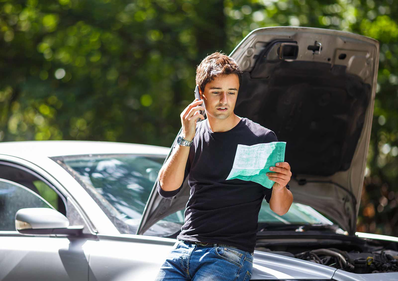 Man reading insurance paper in front of car