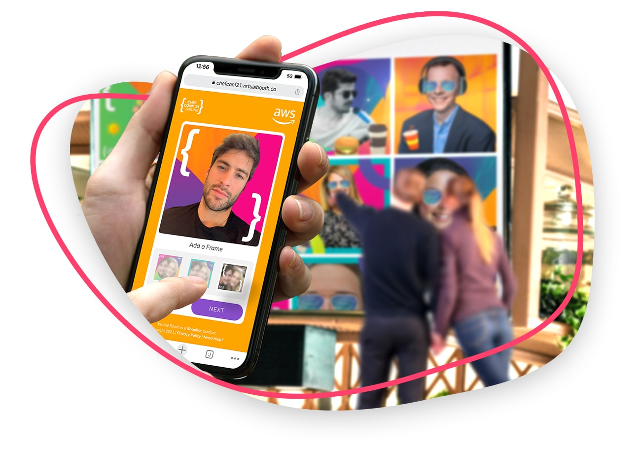 Person holding phone while using a Virtual Photo Booth, with a large screen Digital Mosaic in the background.