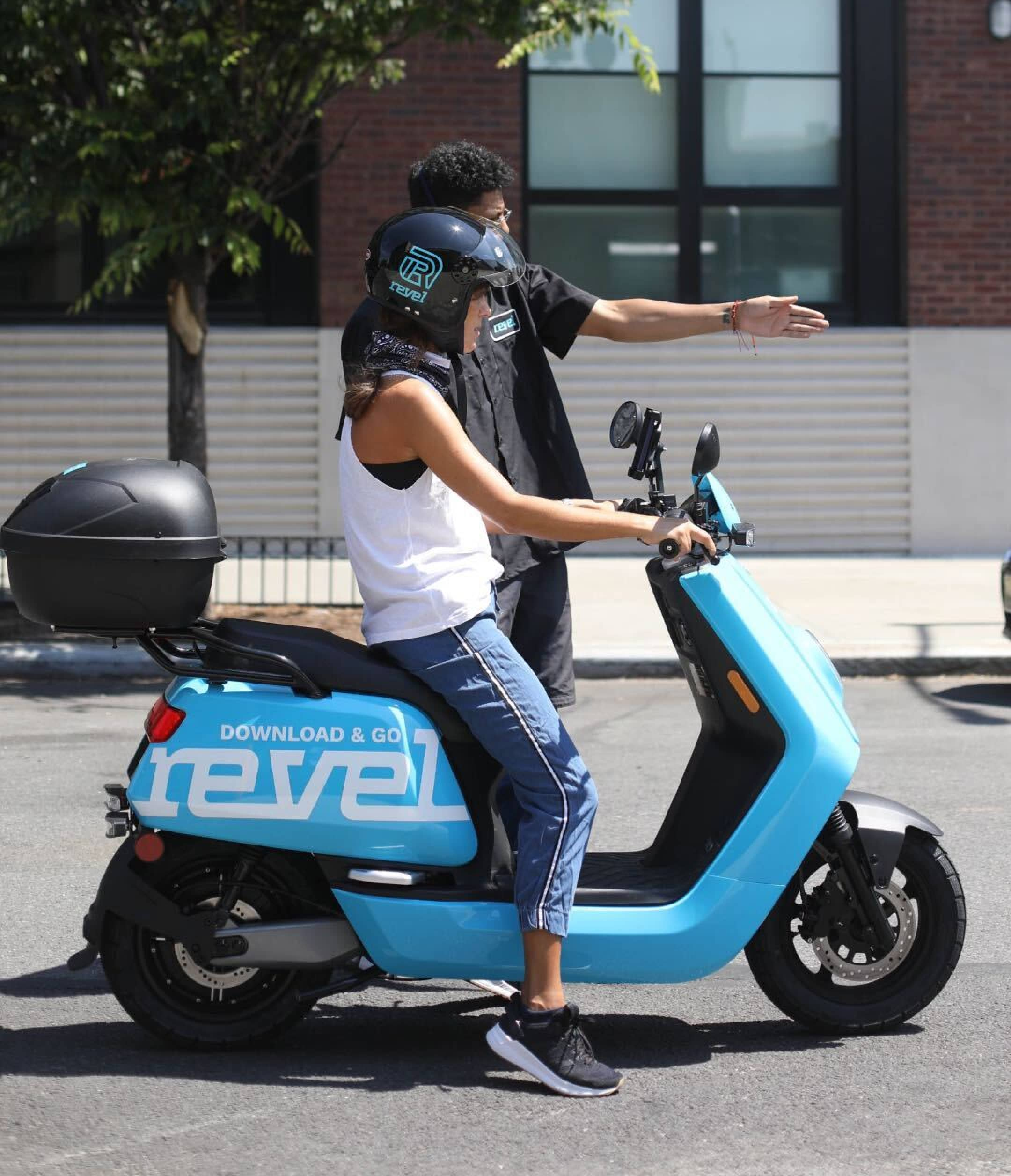 photo of a person teaching another how to ride a revel moped