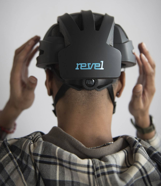 man wearing FEND helmet with revel logo