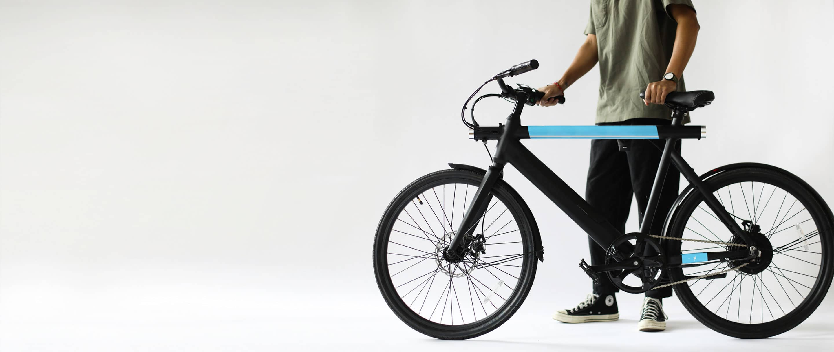 man walking while holding revel ebike