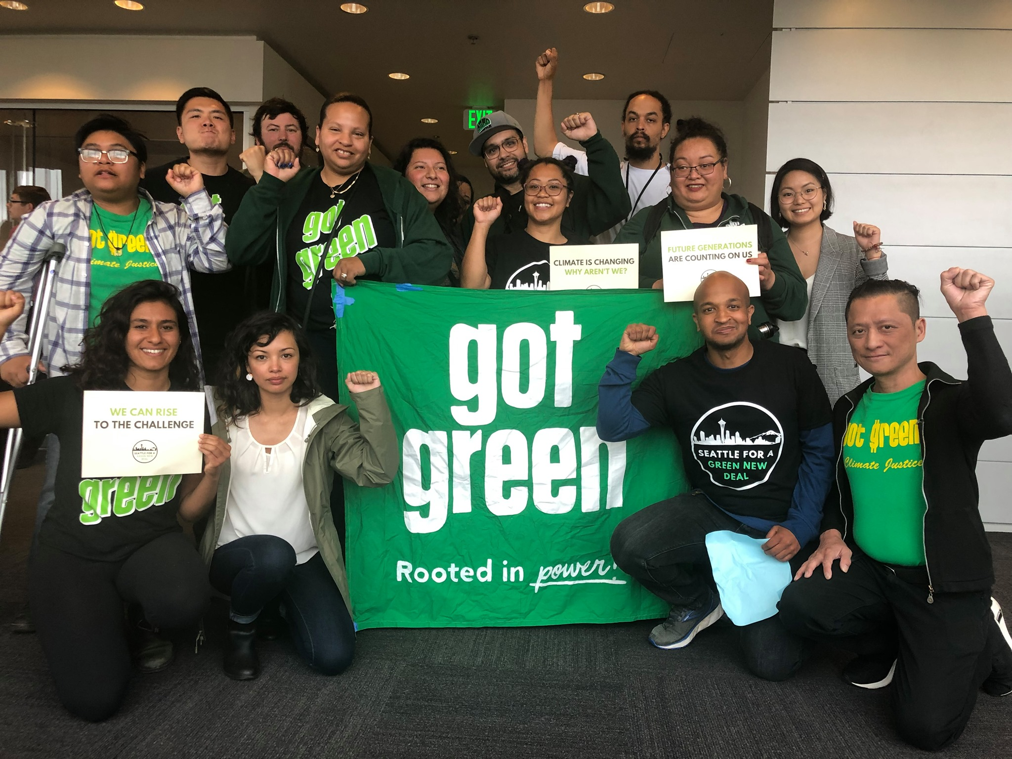 """Group of people in front of a sign saying """"Got Green"""""""