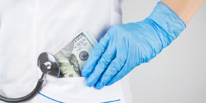 Hand with medical glove putting money in pocket