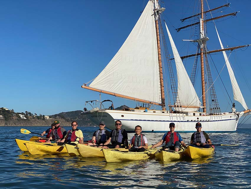 Team members kayaking in front of a sailboat