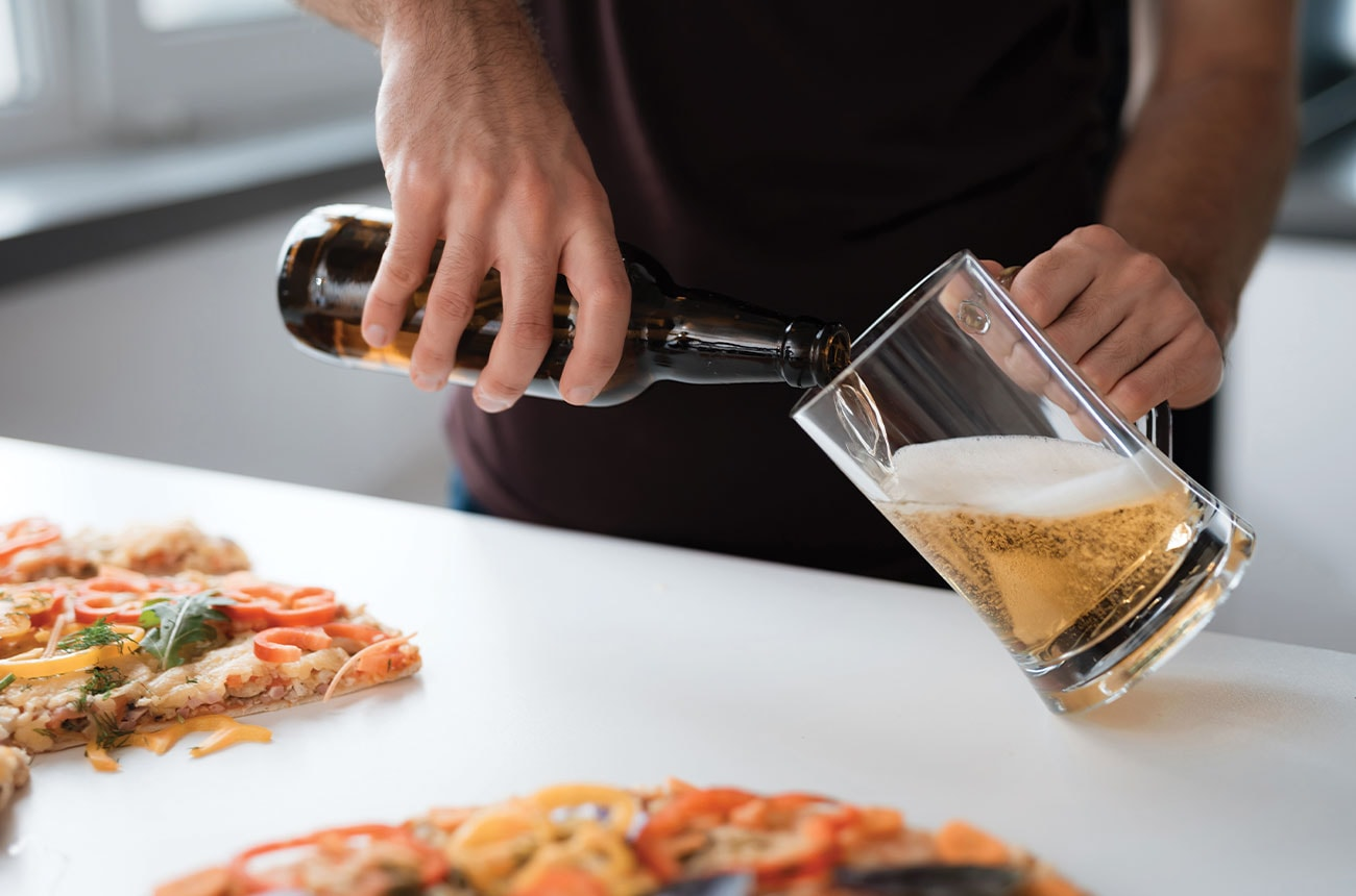 Person pours a beer into a glass next to a pizza.
