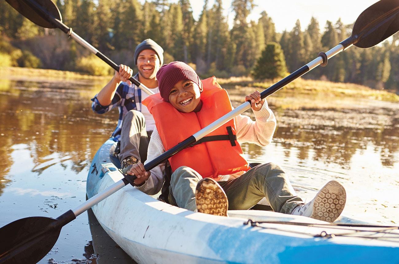 Father and son kayak on a lake.