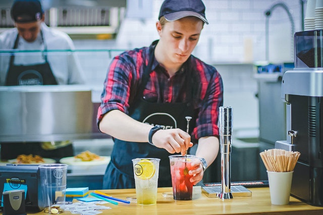 employee mixing drink in kitchen