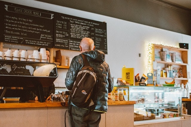 man standing at counter in cafe