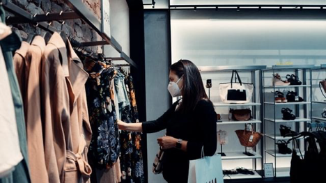 woman shopping at clothing store with mask on