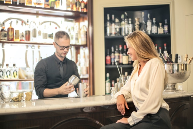 woman sitting at bar with bartender