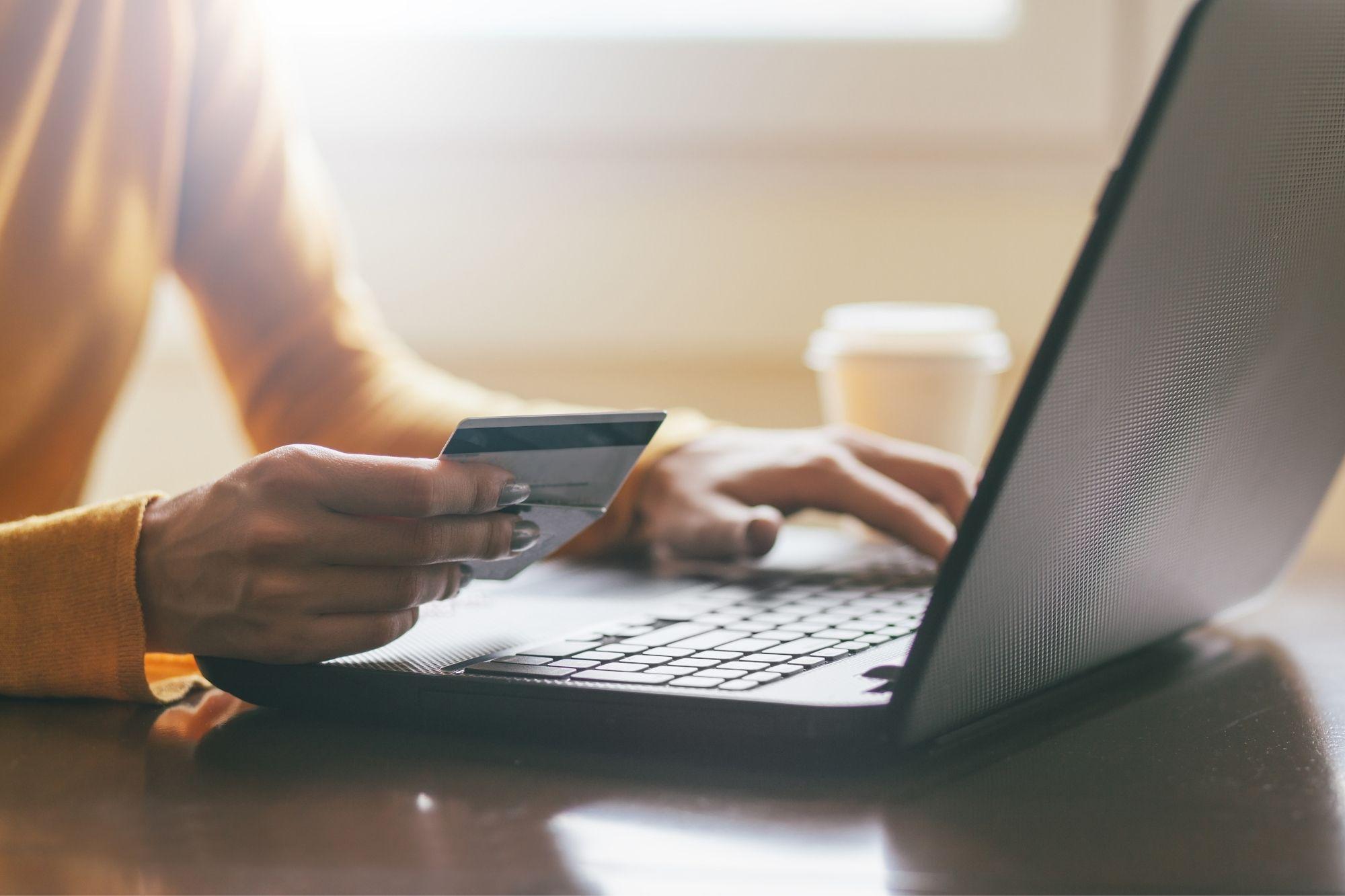 woman holding credit card at computer