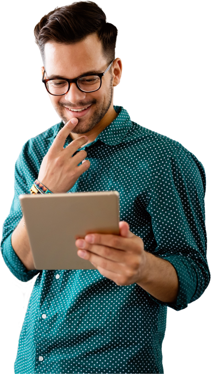 Young male employee smiling with his hand on his chin while looking at a tablet