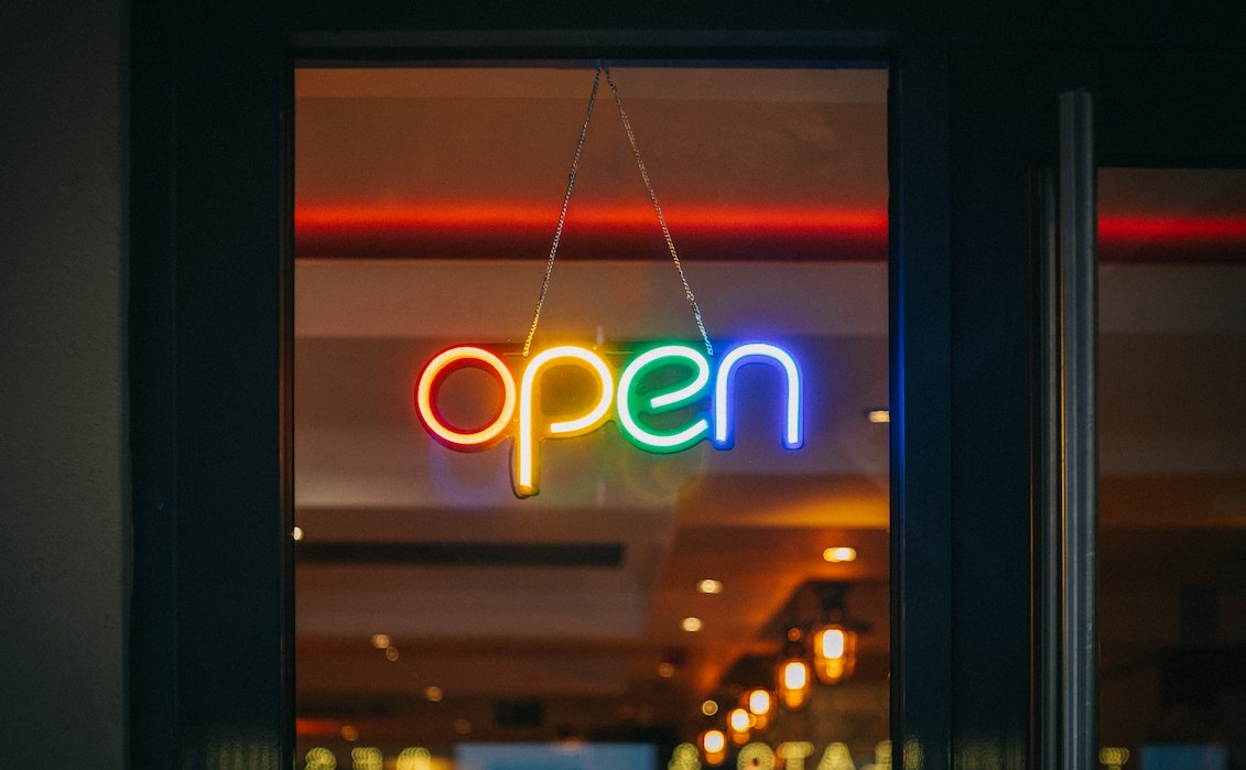 A rainbow colored open sign on window