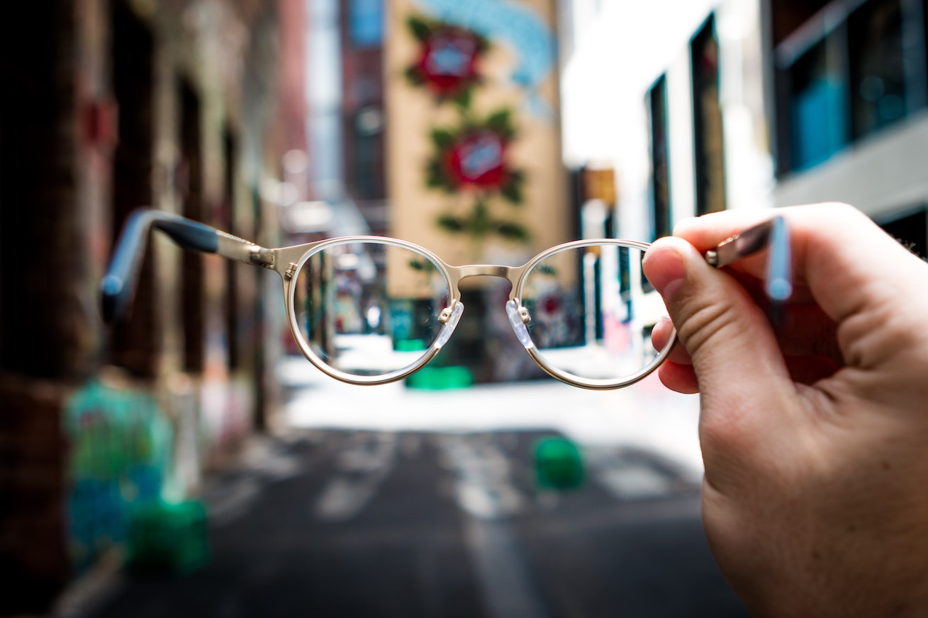 A glasses in front of a photo of a busy city street