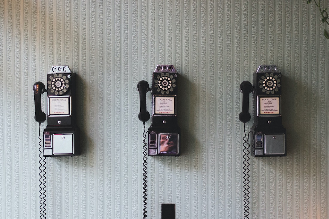 An image of 3 rotary phones on a white wall