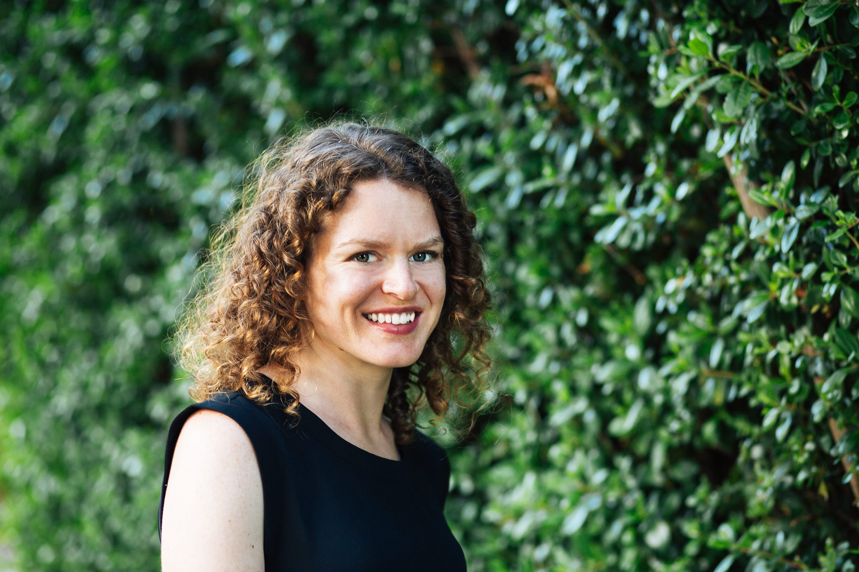 Tara (woman) in front of greenery
