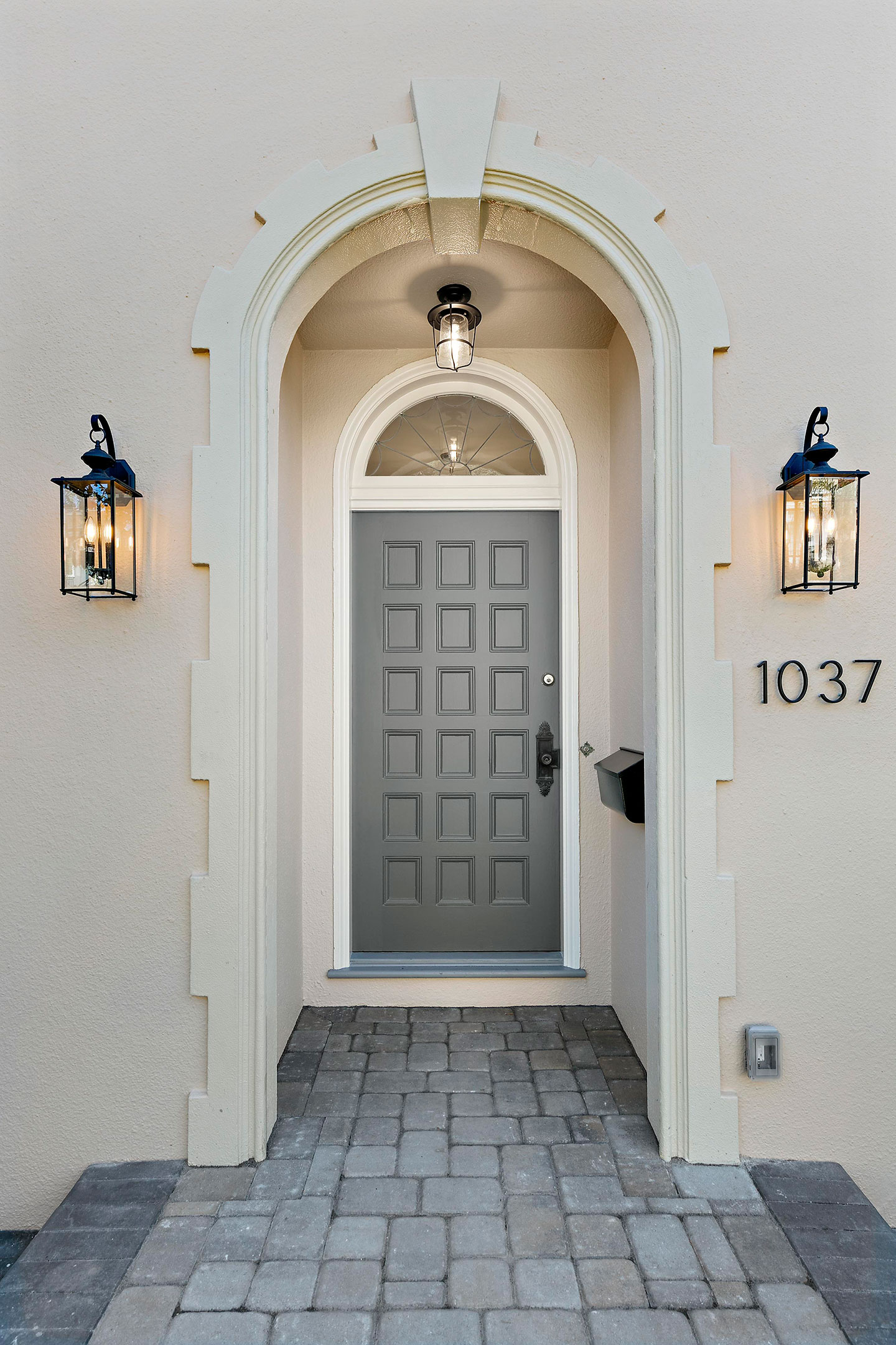 front door view with brick and stucco