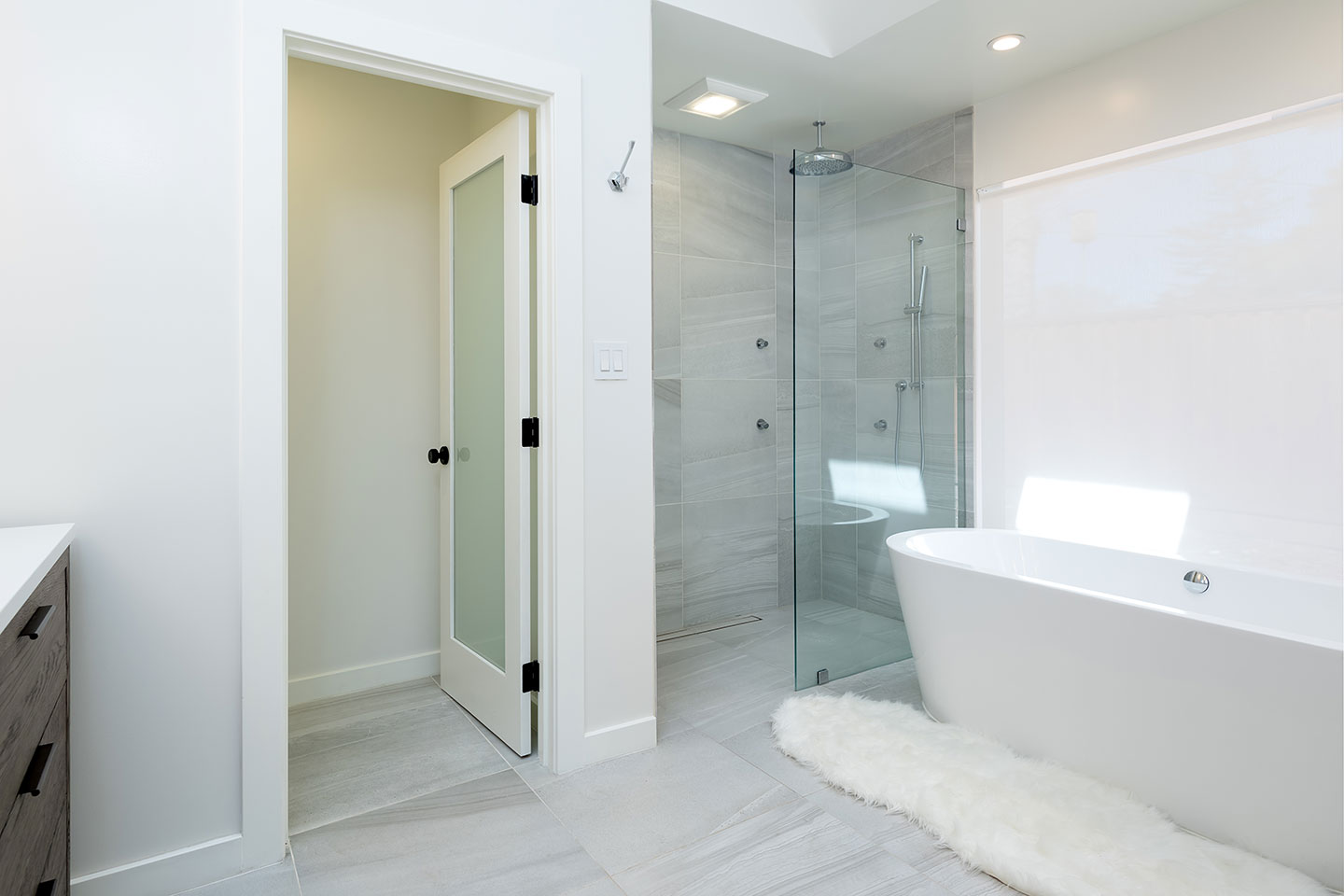 master bathroom with glass enclosed shower and freestanding tub
